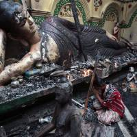 Photo -   A Bangladeshi Buddhist woman prays in front of a damaged statue at a Buddhist temple which was torched during an overnight attack in Ramu in the coastal district of Cox's Bazar, Bangladesh, Tuesday, Oct. 2, 2012. About 1,000 Buddhist families fled their villages after rioters burned at least 10 Buddhist temples and 40 homes and looted shops in anger over a Facebook photo of a burned Quran. Authorities in Bangladesh have ordered security officials to remain alert around official camps of Rohingya Muslims following the attacks.(AP Photo/A.M.Ahad)
