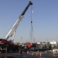 Photo -   A crane lifts a car from the water in Newport, R.I., Friday, Oct. 5, 2012. The U.S. Coast Guard said three people were found inside the car, which was submerged for hours in the Newport shipyard. (AP Photo/Newport Daily News, Matt Sheley)
