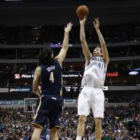 Photo - Dallas Mavericks power forward Dirk Nowitzki (41), of Germany, shoots the ball over Indiana Pacers' Luis Scola (4), of Argentina, during the first half of an NBA game, Sunday, Mar. 9, 2014, in Dallas, Texas. (AP Photo/Jim Cowsert)