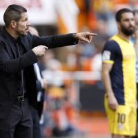 Photo - Atletico's de Madrid coach Diego Simeone from Argentina gestures to players  during a Spanish La Liga soccer match against Valencia at the Mestalla stadium in Valencia, Spain, on Sunday, April 27, 2014. (AP Photo/Alberto Saiz)