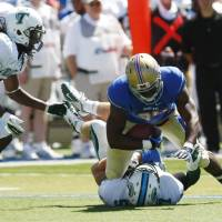 Photo -   Tulane's Devon Walker, far left, watches as teammate Zach Davis takes down Tulsa's Willie Carter during an NCAA colllege football game in Tulsa, Saturday, Sept. 8, 2012. Later in the game, Walker was seriously hurt in a head-to-head collision with a teammate. (AP Photo/Tulsa World, Tom Gilbert) ONLINE OUT; TV OUT; TULSA OUT