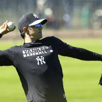 Photo - New York Yankees infielder Brian Roberts throws in the outfield during spring training baseball practice, Monday, Feb. 17, 2014, in Tampa, Fla. (AP Photo/Charlie Neibergall)
