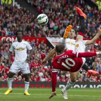 Photo - Manchester United's Wayne Rooney, bottom right, scores against Swansea City during their English Premier League soccer match at Old Trafford Stadium, Manchester, England, Saturday Aug. 16, 2014. (AP Photo/Jon Super)