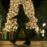 Photo - In this Thursday, Dec. 20, 2012, photo, a holiday shopper walks past a large Christmas tree at Fashion Island shopping center in Newport Beach, Calif. A last-minute surge in spending helped many major U.S. retailers report better-than-expected sales in December, a relief for stores that make up to 40 percent of annual revenue during the holiday period.  (AP Photo/Chris Carlson)