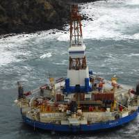 Photo - In this image provided by the U.S. Coast Guard the conical drilling unit Kulluk sits grounded 40 miles southwest of Kodiak City, Thursday, Jan. 3, 2012. The Kulluk grounded after many efforts by tug vessel crews and Coast Guard crews to move the vessel to safe harbor during a winter storm.Calls for federal scrutiny of Royal Dutch Shell PLC drilling operations in Arctic waters swelled Thursday with a request for a formal investigation by members of Congress. (AP Photo/U.S. Coast Guard, Petty Officer 2nd Class Zachary Painter)