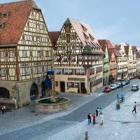 Photo -  The town fountain is flanked by characteristic half-timbered buildings, once filled with grain and corn to enable the town's inhabitants to survive any siege. (Photo credit: Rick Steves)