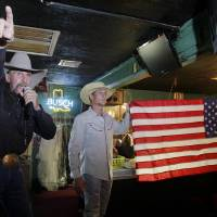 Photo - MURDERS, SHOOTING DEATHS, GIRLS, WELEETKA, TAYLOR PASCHAL-PLACKER, TAYLOR DAWN PASCHAL-PLACKER, SKYLA JADE WHITAKER, TAYLOR PLACKER, SKYLA WHITAKER: Auctioneer Hank Henke (left) from Bonham, TX takes bids on a new donated flag during the benefit auction inside Marvin's Place Bar in Henryetta, OK June 6, 2010, to benefit the families of the slain Weleetka, OK girls two years ago.  MICHAEL WYKE/Tulsa World
