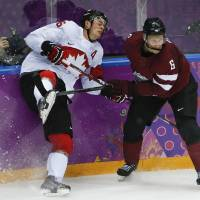 Photo - Latvia defenseman Arvids Rekis checks Canada forward Jonathan Toews during the second period of a men's quarterfinal ice hockey game at the 2014 Winter Olympics, Wednesday, Feb. 19, 2014, in Sochi, Russia. (AP Photo/Mark Humphrey)