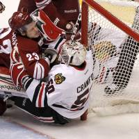 Photo -   Phoenix Coyotes' Oliver Ekman-Larsson (23), of Sweden, collides with Chicago Blackhawks' Corey Crawford (50) during the first period in Game 2 of an NHL hockey Stanley Cup first-round playoff series on Saturday, April 14, 2012, in Glendale, Ariz.(AP Photo/Ross D. Franklin)