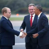 Photo - U.S. President Barack Obama is greeted by Estonia's Minister of Foreign Affairs Urmas Paet, left, and Estonia's Chief of Protocol Toomas Kahur, center, as he arrives in Tallinn, Estonia, Wednesday, Sept. 3, 2014, for a one day visit where he will meet with Baltic State leaders before heading to the NATO Summit in Wales. (AP Photo/Charles Dharapak)