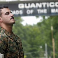 Photo - FILE - In this July 19, 2004 file photo USMC Cpl. Wassef Ali Hassoun prepares himself as he waits to make a statement to a large crowd of media outside the gates to USMC Base Quantico, Va. Nearly 10 years ago Hassoun was declared a deserter after allegedly faking his own kidnapping in Iraq, then reappeared and was to face charges. But he disappeared again in 2005, has now turned himself in to U.S. authorities, and is being flown to the U.S. Sunday, June 29, 2014, from an undisclosed Mideast location. Once at Camp Lejeune, the commander of the 2nd Marine Expeditionary Force will determine whether to court-martial him. (AP Photo/Dylan Moore, File)