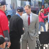 Photo - U.S. Rep. Jim Bridenstine, R-Tulsa, greets Oklahoma veterans as they arrive Tuesday at the World War II Memorial in Washington. Photo by Chris Casteel, The Oklahoman