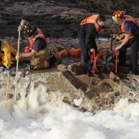 Photo - Rescuers search the Big Sioux River for two adults who went underwater after rescuing a boy who had fallen into the strong current, authorities said, Thursday, March 14, 2013 in Sioux Falls, S.D. (AP Photo/The Argus Leader, Elisha Page)  NO SALES