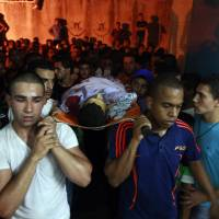 Photo - Palestinians carry the body of Yosuf abu Zaghah, 20, who was killed by the Israeli troops in the West Bank refugee camp of Jenin Early on Tuesday, July 1, 2014. Abu Zaghah, a Palestinian from the militant group Hamas was shot dead when he threw a grenade at forces carrying out an arrest raid in the West Bank hours after the discovery of the bodies of three Israeli teenagers who were abducted over two weeks ago, Israel's military said Tuesday. (AP Photo/Mohammed Ballas)