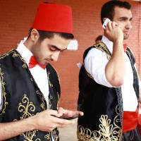 Photo - Cousins Danny Chakron, left, and Nader Chakron take a break from dancing to check their messages at the Lebanese heritage festival sponsored by Our Lady of Lebanon Maronite Catholic Church. PHOTO BY LYNETTE LOBBAN, FOR THE OKLAHOMAN