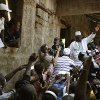 Photo -   Incumbent President Ernest Bai Koroma waves to supporters as he leaves the polling station after voting, in Freetown, Sierra Leone, Saturday, Nov. 17, 2012. A decade after Sierra Leone's brutal civil war, voters on Saturday chose between an incumbent president who has provided new roads and free health care and a field of opposition candidates who decry the poverty and pace of economic recovery.(AP Photo/Rebecca Blackwell)