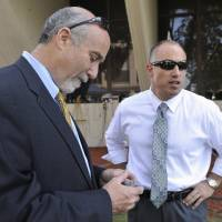 Photo - In this Sept. 6, 2012 file photo, Joel Brodsky, left, and Steven Greenberg, attorneys for former Bolingbrook police officer Drew Peterson, confer outside the Will County Courthouse in Joliet, Ill., during the jury deliberations in Peterson's murder trial. The open lawyerly warfare between Brodsky, the lead counsel and co-counsel Greenberg, who also played a central role in the high-profile case, comes to a head Tuesday, Feb. 19, 2013, at a hearing where a judge will decide if Peterson should get a new trial on grounds that the lead trial attorney allegedly did a shoddy job. (AP Photo/Paul Beaty, File)