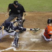 Photo -   Home plate umpire Paul Emmel watches as Miami Marlins' Justin Ruggiano (20) slides safely past Milwaukee Brewers catcher Jonathan Lucroy (20) during the fourth inning of a baseball game in Miami, Monday, Sept. 3, 2012. (AP Photo/J Pat Carter)