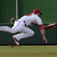 Photo - Washington Nationals left fielder Bryce Harper dives for but misses a ball hit by San Diego Padres' Chris Denorfia during a baseball game at Nationals Park, Friday, July 5, 2013, in Washington. (AP Photo/Alex Brandon)