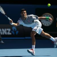 Photo - Novak Djokovic of Serbia hits a forehand return to Fabio Fognini of Italy during their fourth round match at the Australian Open tennis championship in Melbourne, Australia, Sunday, Jan. 19, 2014.(AP Photo/Aaron Favila)