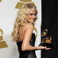 """Photo -  Carrie Underwood poses backstage with the award for best country solo performance for """"Blown Away"""" at the 55th annual Grammy Awards on Sunday, Feb. 10, 2013, in Los Angeles. (AP)"""