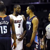 Photo - Miami Heat's Dwyane Wade (3) and Charlotte Bobcats' Ramon Sessions (7) interact after Sessions was called for a foul as referee Zach Zarba (33) watches during the second half of their NBA basketball game, Wednesday, Dec. 26, 2012, in Charlotte. The Heat won 105-92. (AP Photo/The Charlotte Observer, David T. Foster III) MAGS OUT; TV OUT; NEWSPAPER INTERNET ONLY