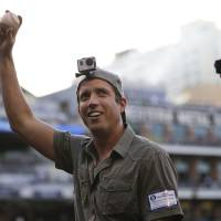 Photo - In this June 6, 2014 photo, GoPro founder and CEO Nick Woodman wears a GoPro camera on his head before throwing out a ceremonial first pitch before a baseball game between the San Diego Padres and the Washington Nationals, in San Diego. GoPro, the maker of wearable sports cameras, loved by mountain climbers, divers, surfers and other extreme sports fans, is expected to start selling its shares for the first time and begin trading on the Nasdaq stock market on Thursday, June 26, 2014. (AP Photo/Gregory Bull)