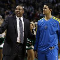 Photo - Boston Celtics head coach Doc Rivers, talks with his son, New Orleans Hornets shooting guard Austin Rivers, prior to an NBA basketball game in Boston, Wednesday, Jan. 16, 2013. (AP Photo/Elise Amendola)