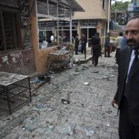 Photo - A Pakistani lawyer talks on his mobile phone at the site of a suicide attack in a court complex, Monday, March 3, 2014 in Islamabad, Pakistan. Two suicide bombers blew themselves up at the complex on Monday, killing 11 people and wounding dozens in a rare terror attack in the heart of Islamabad, officials said. (AP Photo/B.K. Bangash)