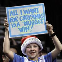 Photo - Denver Nuggets fan Braiden Espinosa holds up a sign during the first quarter of an NBA basketball game with the Portland Trail Blazers in Portland, Ore., Thursday, Dec. 20, 2012. (AP Photo/Don Ryan)