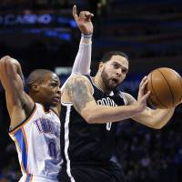 Photo - Brooklyn Nets guard Deron Williams, right, shoots in front of Oklahoma City Thunder guard Russell Westbrook (0) in the first quarter of an NBA basketball game in Oklahoma City, Wednesday, Jan. 2, 2013. (AP Photo/Sue Ogrocki)