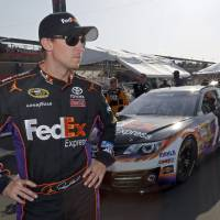 Photo - Denny Hamlin stands in the garage area after taking the pole position in his FedEx Express Toyota for the NASCAR Sprint Cup series Auto Club 400 auto race in Fontana, Calif., Friday, March 22, 2013. (AP Photo/Reed Saxon)