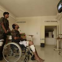 Photo -   Wounded policemen are seen at a hospital following a suicide bomb attack at parade square in Sanaa, Yemen, Monday, May 21, 2012. Officials say Monday's bombing near Sanaa's presidential palace is one of the deadliest attacks in the city in months. (AP Photo/Hani Mohammed)