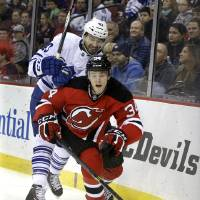 Photo - New Jersey Devils' Jon Merrill (34) goes after the puck as he is hit by Toronto Maple Leafs' Nazem Kadri (43) during the first period of an NHL hockey game, Sunday, March 23, 2014, in Newark, N.J. (AP Photo/Mel Evans)