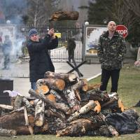 Photo - Local residents chopping wood for a bonfire as Russian soldier guards the gate of an Ukrainian infantry base in Perevalne, Ukraine, Tuesday, March 4, 2014.   Tensions remained high in the strategic Ukrainian peninsula of Crimea with troops loyal to Moscow firing warning shots to ward off protesting Ukrainian soldiers. (AP Photo/Sergei Grits)
