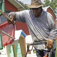 Photo -  Kenneth Tisdale of Tisdale's Lawns & More mows in south Oklahoma City in Tuesday's hot weather. Photo by K.T. King, The Oklahoman   KT King