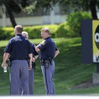 Photo - Police officers stand outside WMAR-TV, after a truck driven by a man rammed the Baltimore-area television station Tuesday, May 13, 2014 leaving a gaping hole in the front of the building, in Towson, Md. Police were still searching for the driver. They said they didn't know of a motive and didn't find weapons in the truck, but they assumed the driver may be dangerous because he ran into the occupied building.  The station believes everyone inside evacuated safely, News Director Kelly Groft said. (AP Photo/Steve Ruark)