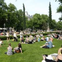 Photo - In this June 26, 2013 photo, people cool off on a hot summer day in Esplanade Park in Helsinki, Finland. In summer, glorious sun-filled days draw picnickers to every available last patch of grass. (AP Photo/Lehtikuva, Martti Kainulainen) FINLAND OUT
