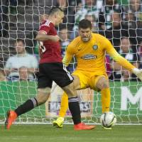 Photo - Legia Warsaw's Michal Kucharczyk, left, scores past Celtic's Fraser Foster during their Champions League qualifying soccer match at Murrayfield, Edinburgh, Wednesday Aug. 6, 2014. (AP Photo/PA, Jeff Holmes) UNITED KINGDOM OUT  NO SALES  NO ARCHIVE