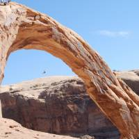 Photo - FILE - This Nov. 4, 2012, file photo, shows an unidentified person swinging from the Corona Arch near Moab, Utah. The federal government is asking for people to weigh in on whether it should temporarily ban daredevil rope swinging and other activities from iconic arches in Moab. The Bureau of Land Management says rope recreation at Corona Arch and Gemini Bridges may be disturbing other people in popular hiking areas that each get more than 40,000 visitors a year. The BLM is accepting written and emailed comments through Sept. 25, 2014. (AP Photo/The Salt Lake Tribune, Brian Maffly) DESERET NEWS OUT; LOCAL TV OUT; MAGS OUT