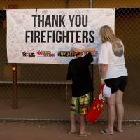 Photo - Ten-year-old Lyam Davis, left, watches as his mother, Rachel Davis, both of Phoenix, Ariz., sign a banner during the Fourth of July celebration at Pioneer Park, Thursday, July 4, 2013 in Prescott, Ariz. in honor of the 19 fallen Granite Mountain Hotshot firefighters who died fighting a blaze near Yarnell, Ariz. on Sunday. On a day meant to ponder the nation's birth, and those who built and defended it over 237 years, Prescott's residents had 19 of their neighbors, their friends, their relatives to remember. (AP Photo/Julie Jacobson)