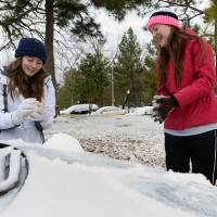 Photo - Stephen F. Austin State freshmen Tara Ramsey, left, of Mont Belvieu, Texas, and Makenzie Dickins of Livingston, Texas, build a miniature snowman on the hood of a car Friday, Jan. 24, 2014 on the SFA campus in Nacogdoches, Texas. The girls were enjoying an unexpected day off after campus offices were closed and classes were cancelled due to a winter storm that moved through the area overnight. (AP Photo/The Daily Sentinel, Andrew D. Brosig) MANDATORY