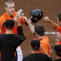 Photo - Oklahoma State's Kevin David celebrates with his teammates after he scores the go-ahead run against Oklahoma during the fourth inning their game at the AT&T Bricktown Ballpark in Oklahoma City on Sunday, May 10, 2009. The Cowboys beat the Sooners 5-1. Photo by John Clanton