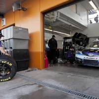 Photo - A pit crew member for Denny Hamlin rolls new tires into the garage before qualifying for the NASCAR Sprint Cup Series auto race, Friday, March 8, 2013 in Las Vegas. (AP Photo/Julie Jacobson)