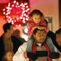 Photo - Lae-lee Amevor sits on the shoulders of her father, Solomon Amevor, while waiting for a sleigh ride during the holiday lighting ceremony at Rose State College. Photos by Nate Billings, The Oklahoman