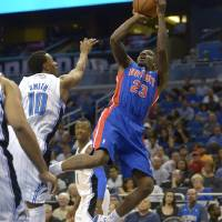 Photo - Detroit Pistons guard Walker Russell (23), right, goes up for a shot in front of Orlando Magic guard Ishmael Smith (10) during the second half of an NBA basketball game in Orlando, Fla., Monday, April 9, 2012.(AP Photo/Phelan M. Ebenhack)