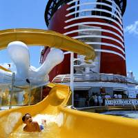 Photo - Mickey's Pool, a favorite feature of the Disney Cruise Line fleet, features a Mickey Mouse-shaped pool and an oversized version of Mickey's hand supporting a yellow winding slide that splashes down into the pool area. PHOTO PROVIDED.  Disney Cruise Line - Disney Cruise Line