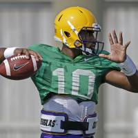 Photo - LSU quarterback Anthony Jennings (10) passes during their NCAA college football practice in Baton Rouge, La., Wednesday, Aug. 6, 2014. (AP Photo/Gerald Herbert)