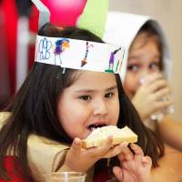 Photo - Left: Nizhoni Gould, left, eats bread topped with homemade butter as Guadalupe Munoz looks on. Kindergartners at Rancho Village Elementary School in Oklahoma City had a Thanksgiving celebration Tuesday. Photos by Jim Beckel,  The Oklahoman