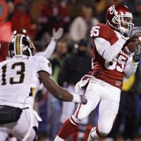 Photo - CELEBRATE / CELEBRATION: Oklahoma's Ryan Broyles (85) makes a reception in front of Missouri's Kenji Jackson (13) during the first half of the Big 12 Championship college football game between the University of Oklahoma Sooners (OU) and the University of Missouri Tigers (MU) on Saturday, Dec. 6, 2008, at Arrowhead Stadium in Kansas City, Mo.   PHOTO BY NATE BILLINGS, THE OKLAHOMAN  ORG XMIT: KOD